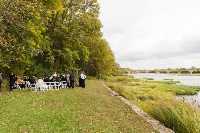Outdoor wedding ceremony beside a river bank
