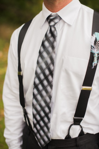 Groomsmen wearing black pants, suspenders and plaid skinny tie and a feather boutonniere