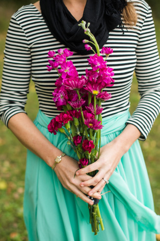 Bridesmaid holding purple flowers wearing a teal skirt and black and white top