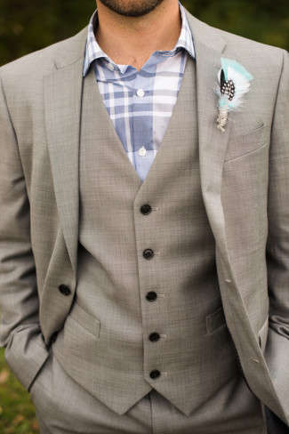 Groom wearing a grey suit with a plaid blue top and a feather boutonniere