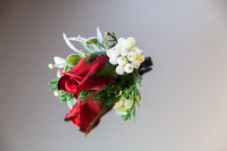 Red rose boutonniere with white hypercum berries