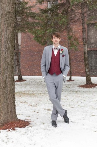 Groom standing in snow wearing gray suite and red vest