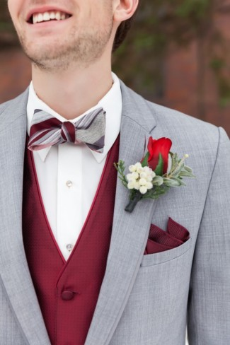 Groom wearing gray suit, maroon vest, red rose boutonniere and bow tie