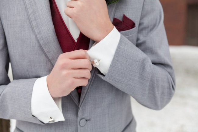 Groom wearing gray suit with red pocket square and silver cuff links