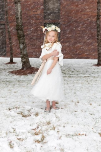 Flower girl standing in the snow wearing flower crown and silver shoes