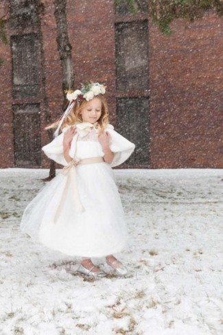 Flower girl twirling in the snow wearing flower crown and silver shoes