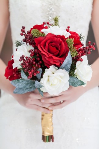 Bride carrying a red and white rose bouquet with red berries