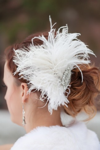 Bride wearing her hair in a bun with a feather and rhinestone hair piece