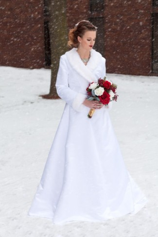 Bride standing in the snow while it snows all in white holding red bridal bouquet