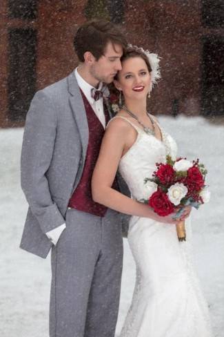 Groom wearing gray suit and bride holding red bridal bouquet and leaning against once another in snow