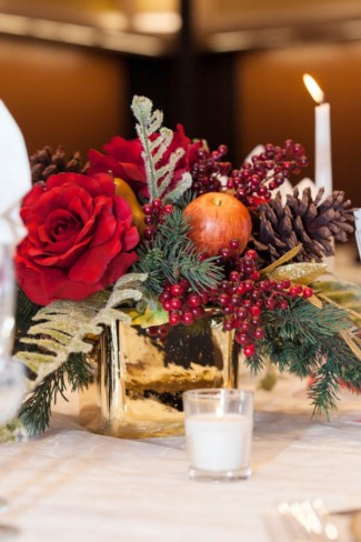 Red roses, pine cones, red berries and ever green in gold vase for wedding reception centerpiece