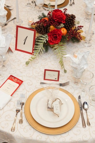 Winter wedding reception with gold chargers and red munu and table number