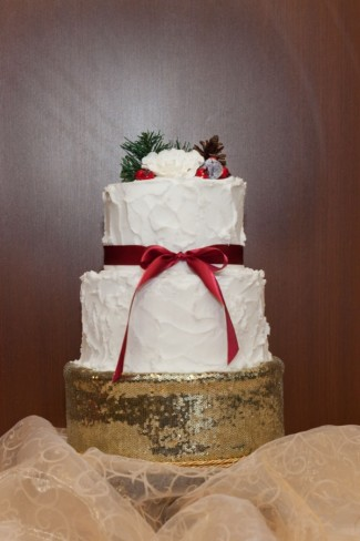 2 Tier white wedding cake on a gold stand with a red ribbon