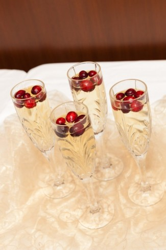 4 champagne glasses full of Champagne and red cranberries