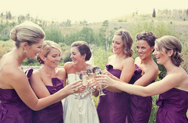 bridesmaids in dark purple dresses toast with champagne
