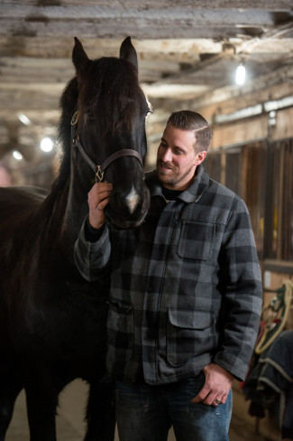 man wearing blue and black plaid standing beside a black horse