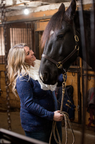girl wearing a blue sweater and white scarf looking up at a black horse