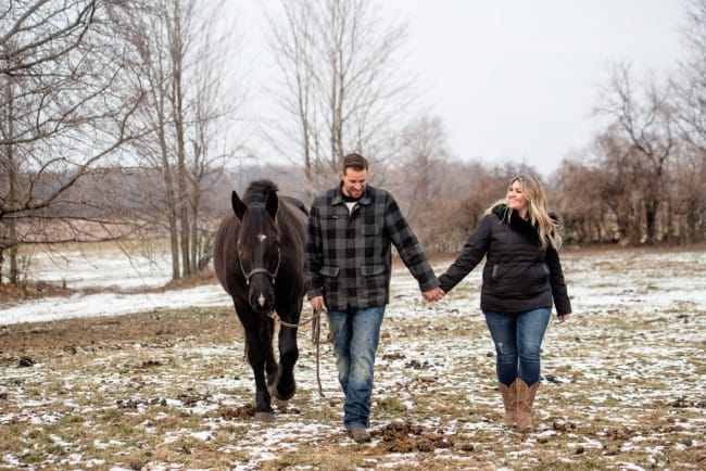 couple walking across a frozen field with their black horse while holding hands