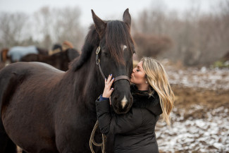women kissing her horse in a frozen field