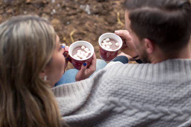 couple wrapped with a grey blanket and drinking hot chocolate