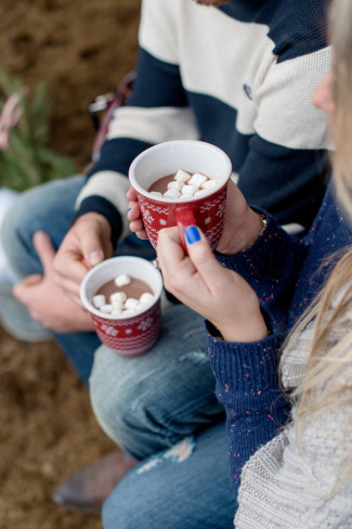 Couple holding red sweater mugs with hot chocolate and mini marshmallows