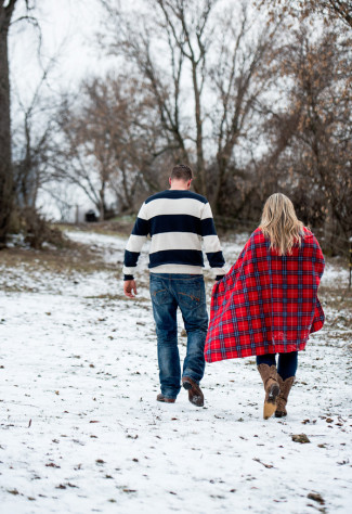 Couple walking in frozen field hand in hand wrapped in a red plaid blanket