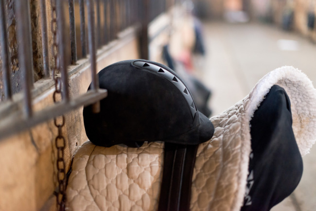 Horse riding stable with horse saddle hanging on wall with a riding helmet