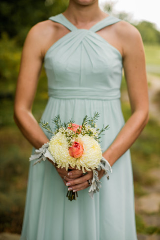 bridesmaid holding bouquet of Dusty Miller, China Mums, and peach roses
