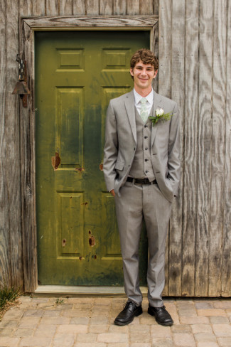 groom standing outside wood door at morning glory farms
