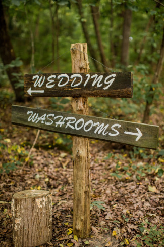 "wood arrow signpost with words ""wedding"" and ""washrooms"""