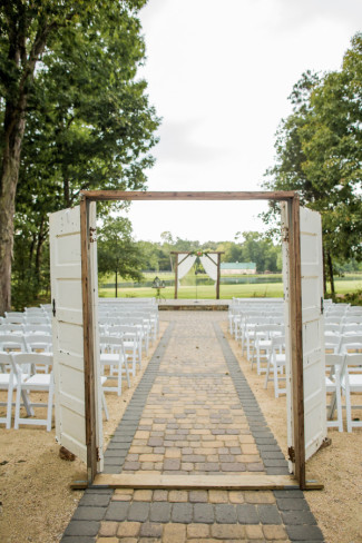 white doors in frame as entrance to wedding aisle at morning glory farms