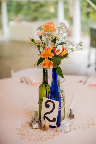 table number blue bottle with peach roses and babys breath
