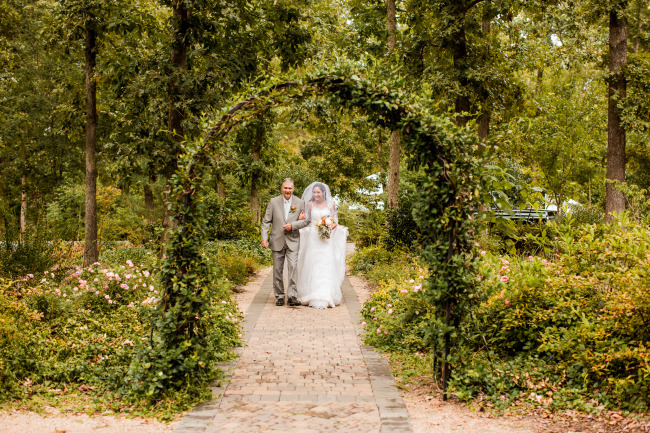 bride and her father walk down the brick path