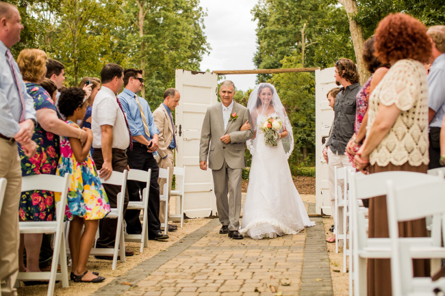 bride and father walk down aisle arm in arm