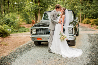 bride and groom kiss in front of old truck on gravel road