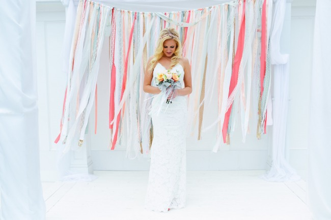 bride standing in front of ribbon and lace ceremony backdrop