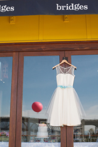 wedding dress hangs on door at Bridges Restaurant in Granville Island