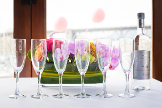 champagne flutes lined up with floral arrangement behind