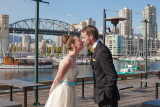 bride and groom touch noses on patio with Burrard Bridge in background