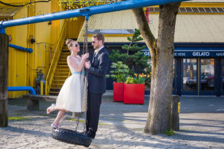 bride and groom stand on tire swing together