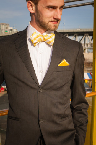 Groom in yellow striped bow tie and dark grey suit