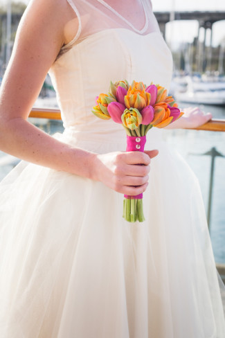 bride holds bouquet of colorful tulips