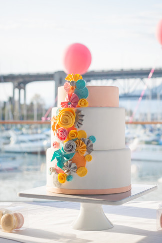 wedding cake with colorful pinwheel designs and Granville Island in background