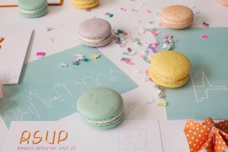 macaroons laying on custom wedding stationery with sprinkles