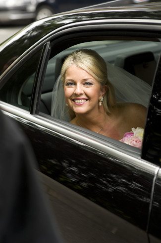 Bride sitting in a Mercedes looking out the window smiling on her way to the church