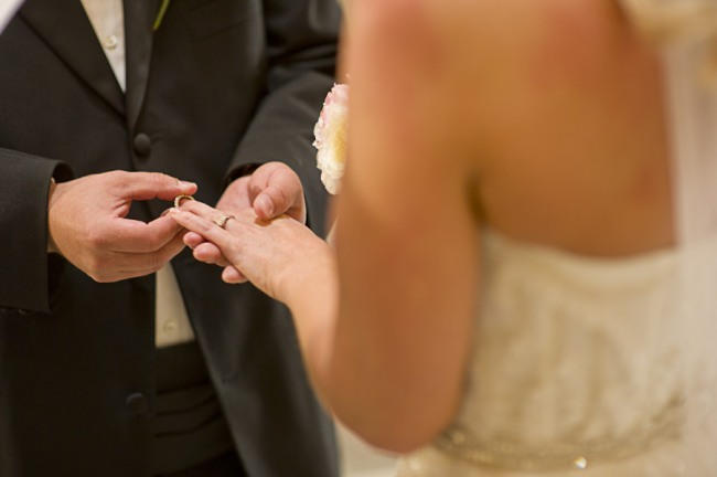 groom putting ring on brides finger during wedding elopement in Paris