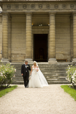Newlyweds walking on gravel path outside of Chapelle Expiatoire, Paris, France