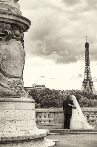 Bride and groom with their back faced toward the camera looking at Eiffel tower