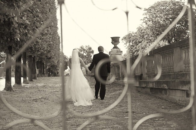 Bride wearing a Monique Lhuillier gown holding hands with groom wearing tux with a rod iron gate infront
