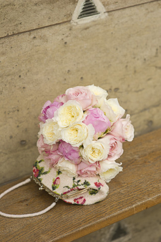 pink and white flower bouquet placed on top of a vintage beaded small purse